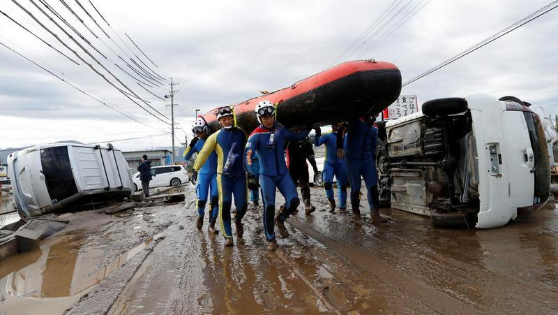 Rescue workers carry a rubber dinghy as they search a flooded area at the Chikuma River in Nagano Prefecture, Japan, October 14, 2019. Reuters