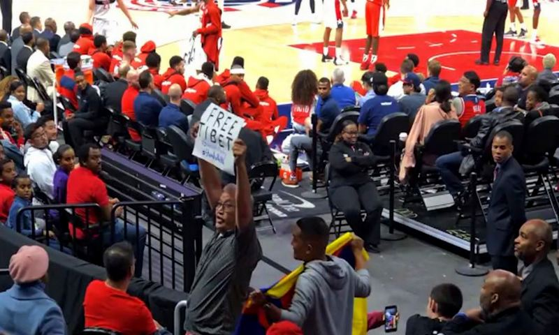 "Tenzing Barshee with a placard saying ""Free Tibet"" and his friend James San Mateo with the Tibetan flag at the NBA game in Washington, D.C. on October 9, 2019. Photo: Youtube Screenshot"